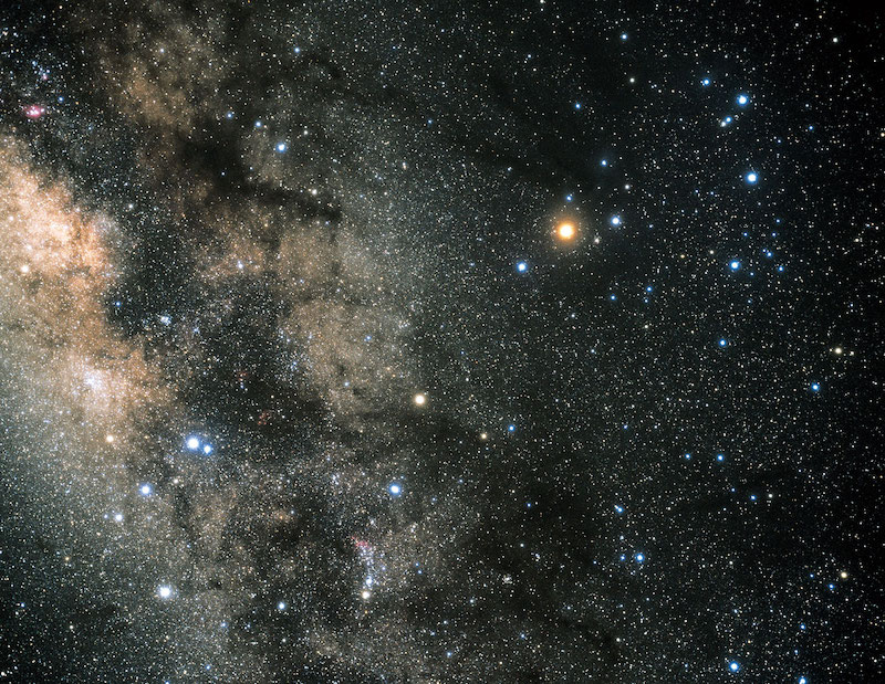 Dense star field with brighter stars in the constellation Scorpius with part of the nebulous Milky Way.