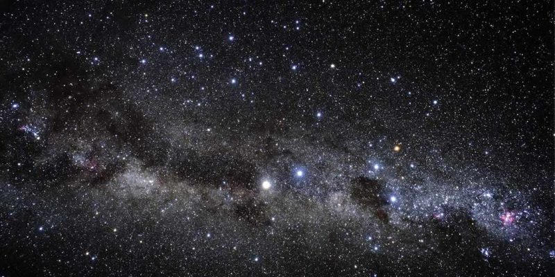 A wide view of a star field with a few bright stars and many faint ones and the Milky Way running across.