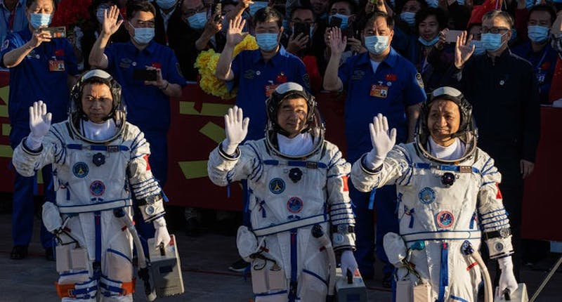 Three astronauts in space suits standing in front of a crowd, waving.