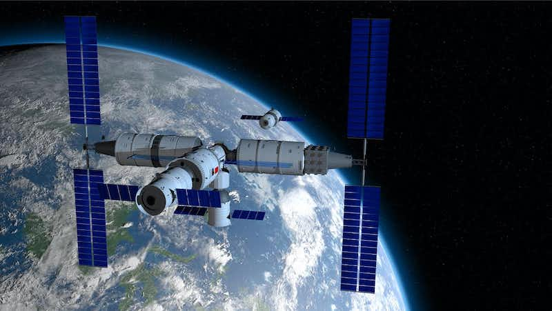 Three connected cylindrical modules with blue solar panels, floating above planet Earth.