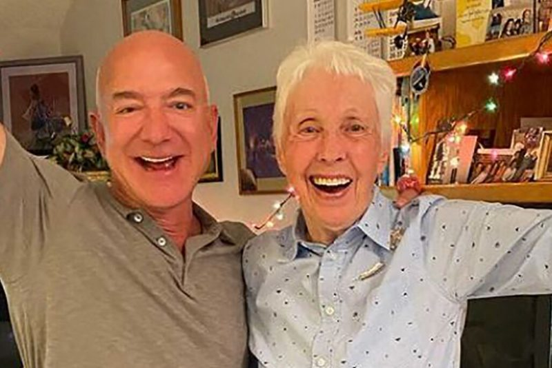 A bald man, and a gray-haired woman, with their arms around each other, with big triumphant smiles.