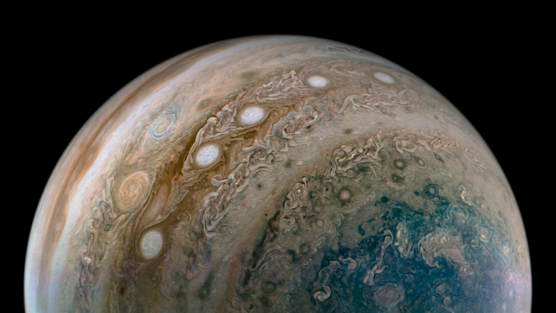 Planet Jupiter seen close up, with a string of 5 white ovals visible on its surface amid parallel swirly bands.