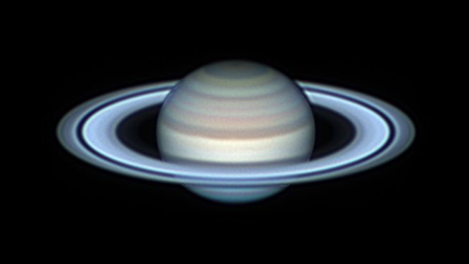 Beautiful telescopic image of Saturn showing bands and multiple rings in pastel tones.