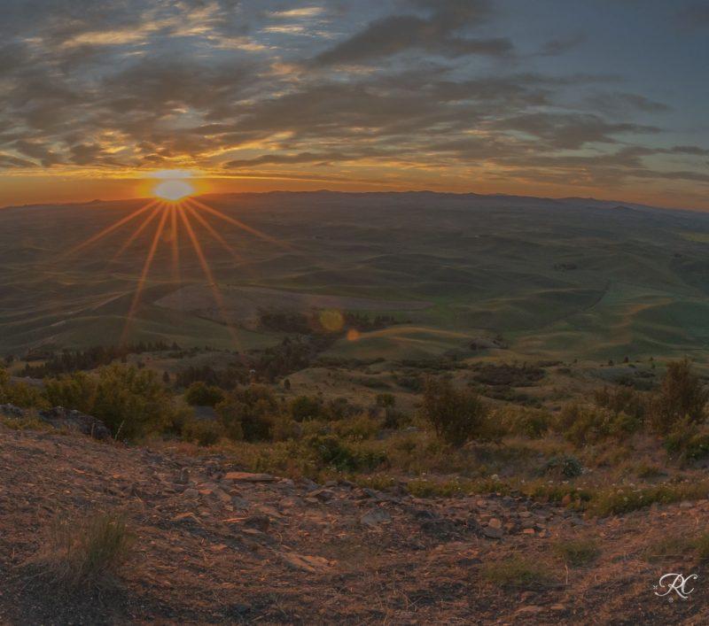 A distant sunrise under light clouds, seen across rolling hills.
