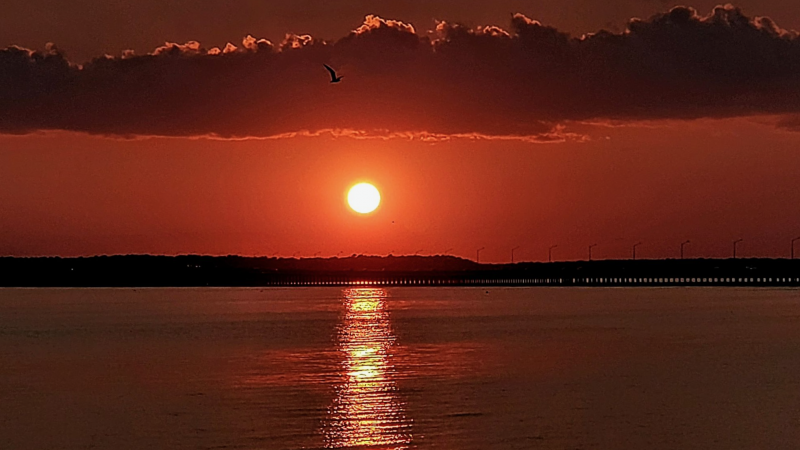 A very red sunset, in a red sky, over water, with a reflection of the sun in the water.