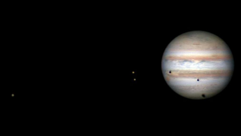 A telescope view of Jupiter, with 3 dots to one side (the moons) and 3 dark dots on Jupiter's face (the moons' shadows).