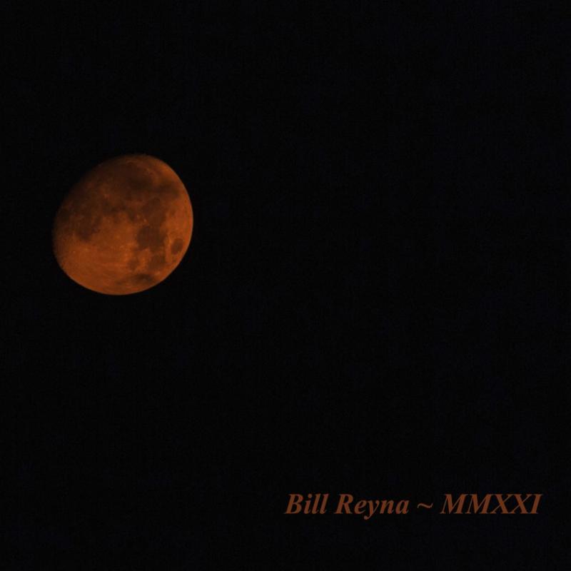 A very deep orange-red waxing gibbous moon in a dark sky.