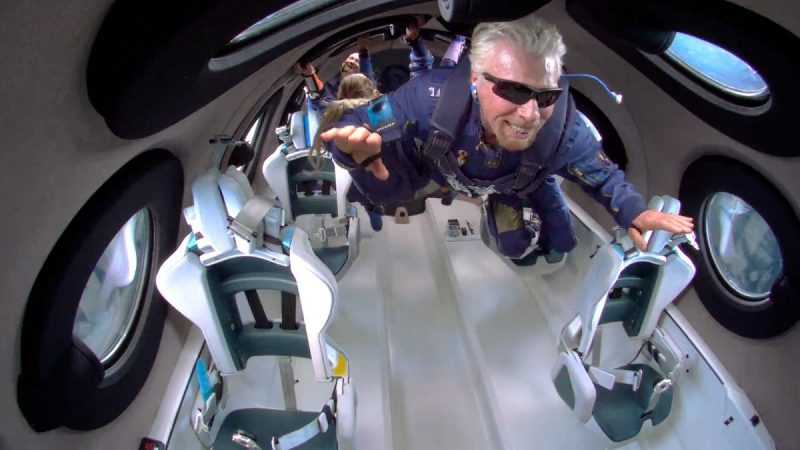 Billionaire space race: A man with white hair and wearing a blue spacesuit is floating in the cabin of a spaceplane.