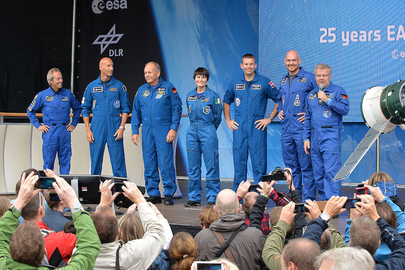 ESA: Seven people in blue suits stand in a line on a stage. One is speaking into a microphone.