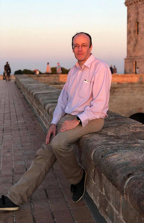Man in slacks and long-sleeve shirt sitting on stone wall in sunset light.