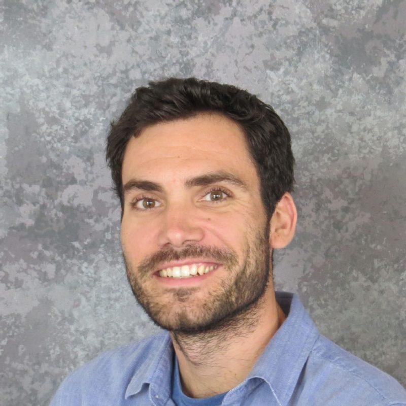 رجل في منتصف العمر مبتسم ذو شعر داكن ولحية قصيرة ، يرتدي قميصًا أزرق مفتوح الياقة.