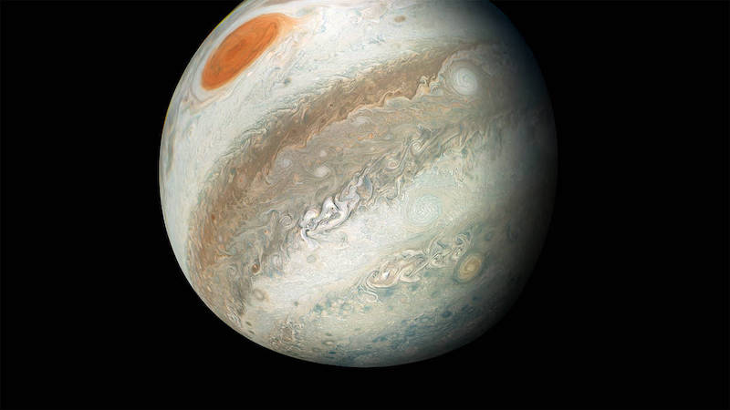 Planet with broad bands of clouds and large red spot, on black background.