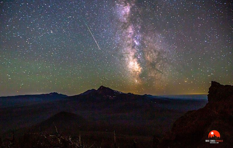 Perseid photos: A starry green and purple sky with a thin, bright white streak across the middle over dark mountains.