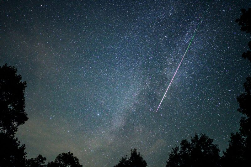 Slash of nearly-white light changing from pale green to magenta alongside Milky Way in very starry sky.