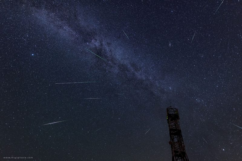 Panoramic view of the night sky with the Milky Way and multiple Perseid meteors.