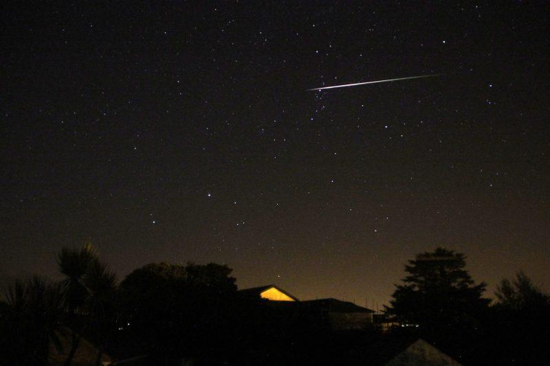 Perseid meteor horizontal across top of dark sky.