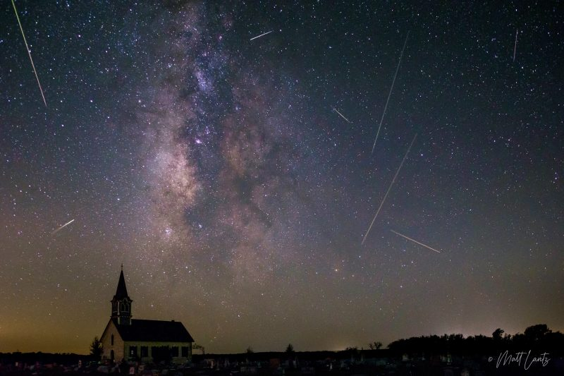 Milky Way over church with many meteor streaks.