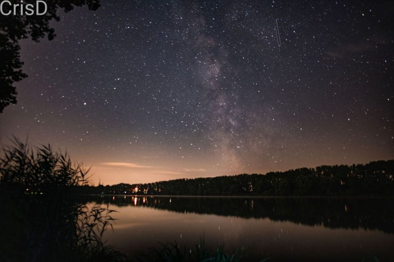 Milky Way over lake with two vertical thin lines of meteors next to it.