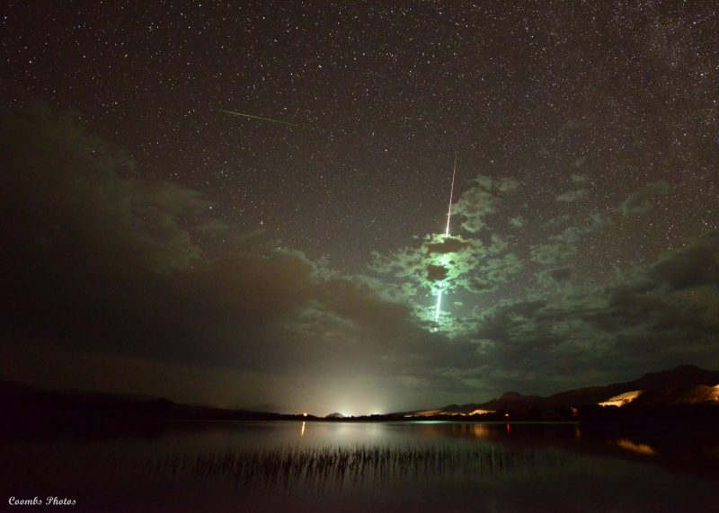 Bright streak of light lights up clouds in front.