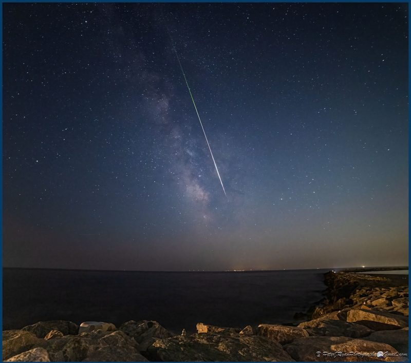 Panoramic view of the night sky with the Milky Way and a bright Perseid meteor.
