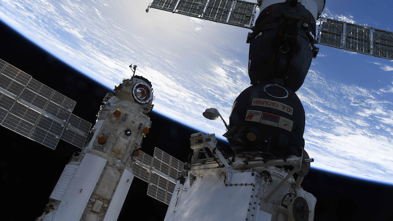Nauka module: A cylindrical white spacecraft next to a black spacecraft with Russian writing. Both float in space above Earth.