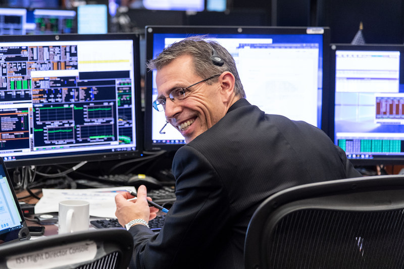 A man with ash brown hair, sitting in a chair and broadly smiling in front of several computer screens.