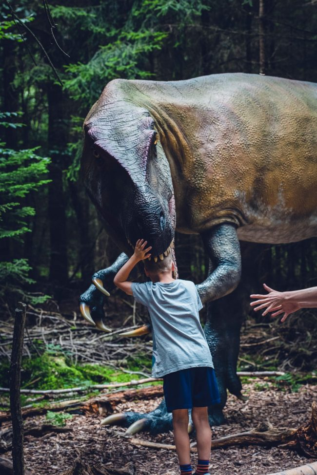 Kid's head in dinosaur's mouth and a person's hands reaching for kid.