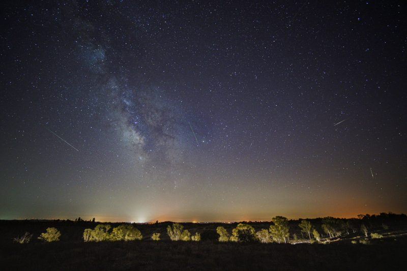 Milky Way and multiple meteor streaks in starry sky.