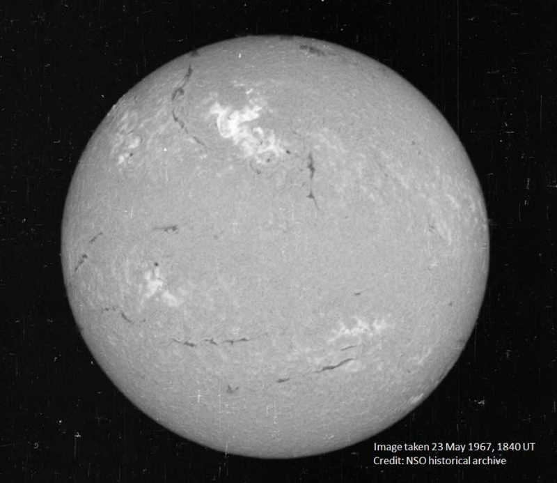 The sun observed in H-alpha, looking like a marble-like orb, with the 1967 solar storm at the center top.