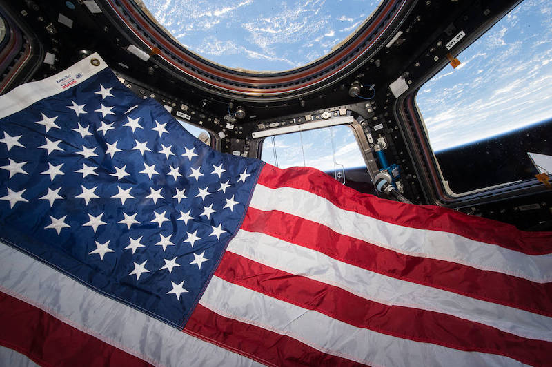 American flag floats in a chamber with several large windows and a view of Earth far below.