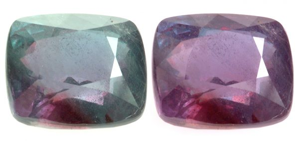 Two faceted gemstones, one greenish and the other purplish.