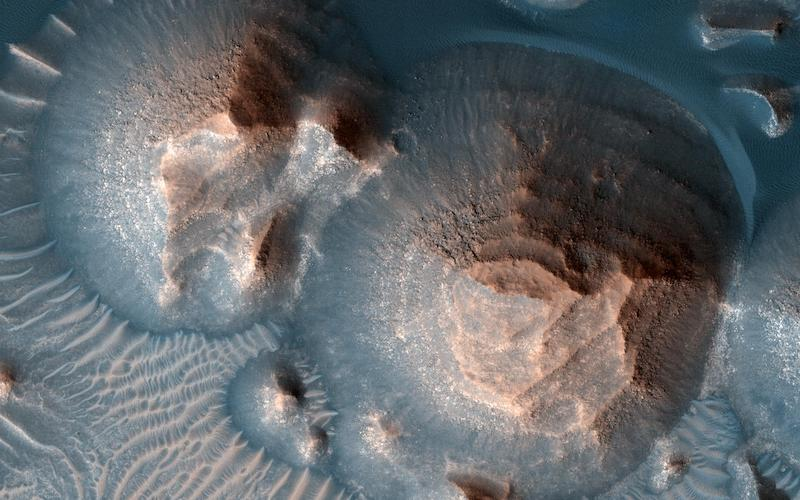 Volcanic calderas with layered, rocky mounds inside them.