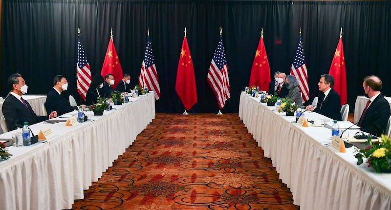 U.S. and China: Chinese men sit at a long table to the left, Americans at a table to the right. National flags in background.