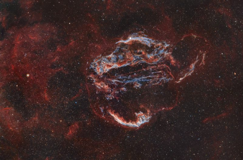September deep sky: White and blue tendrils surrounded by reddish filaments and haze.