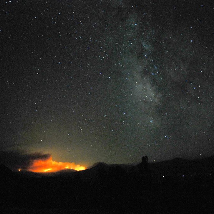 Wildfire threatens a SETI telescope: A dark night sky, with a fire burning in the distance.