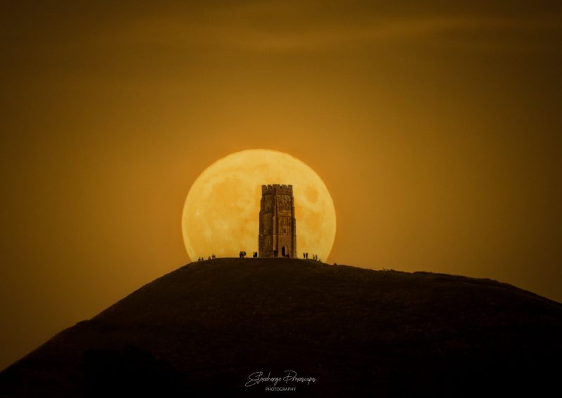 2021's Harvest Moon: A yellow full moon rising behind a single square, stone tower.