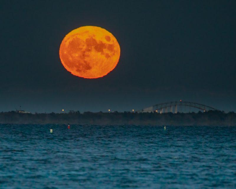 Big orange Harvest Moon rising over blue ocean with arc-shaped bridge in distance.