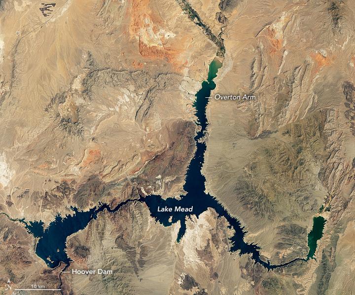 NASA drought research: Satellite view of dark blue, long, skinny lake in desert landscape.