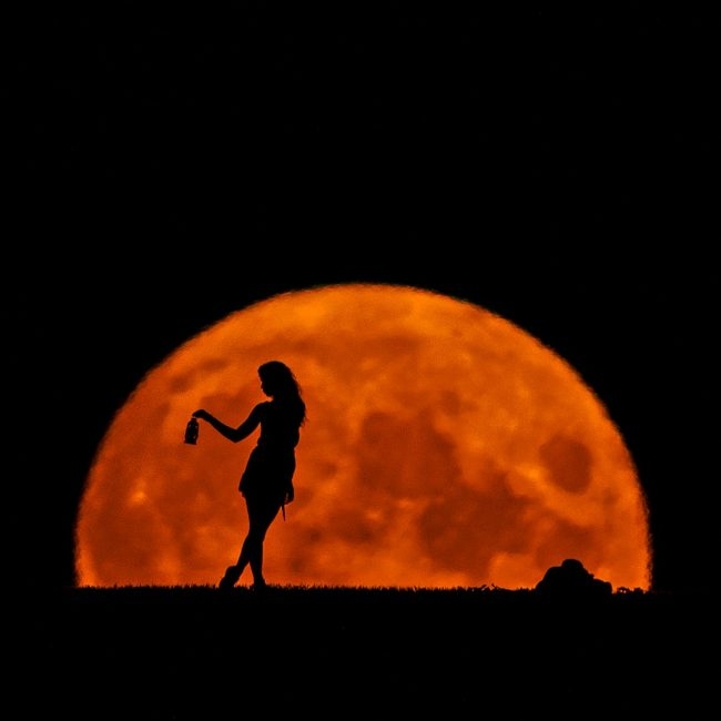 Close-up of the harvest full moon with the silhouette of a young woman.