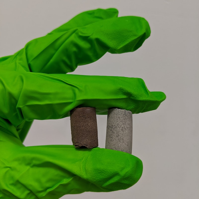 Fingers in bright green plastic glove hold small concrete cylinders, one reddish and the other gray.