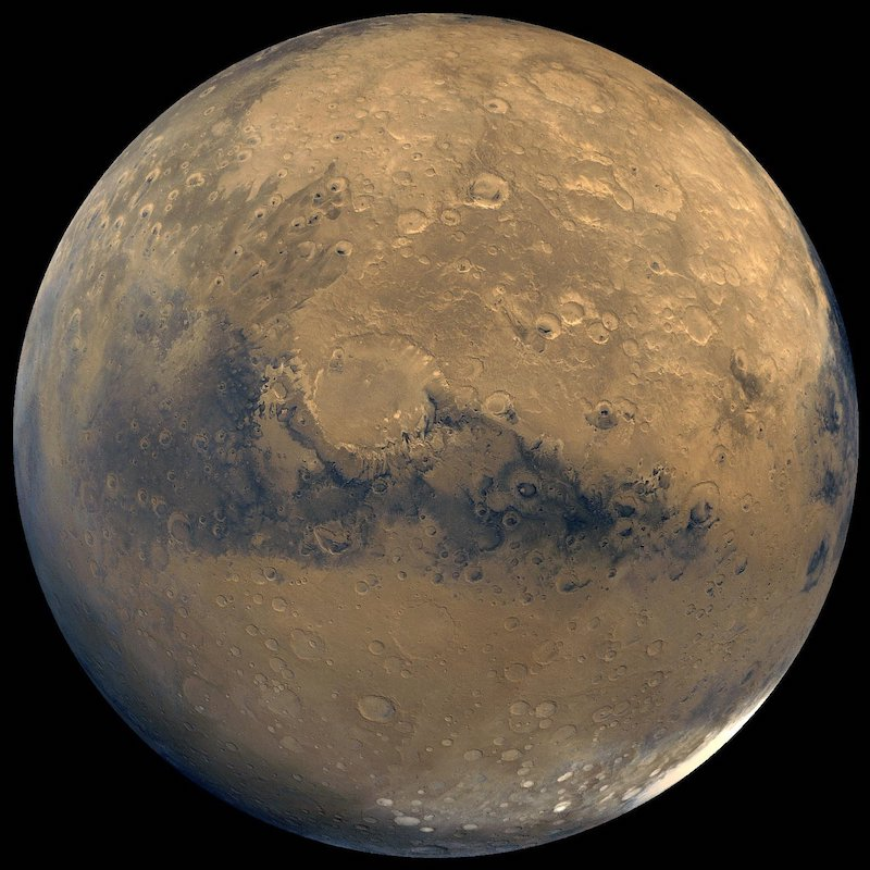 Reddish rocky planet with dark patches and bright white polar cap in lower right.