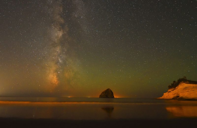 Vertical Milky Way with green and orangish glow over ocean.