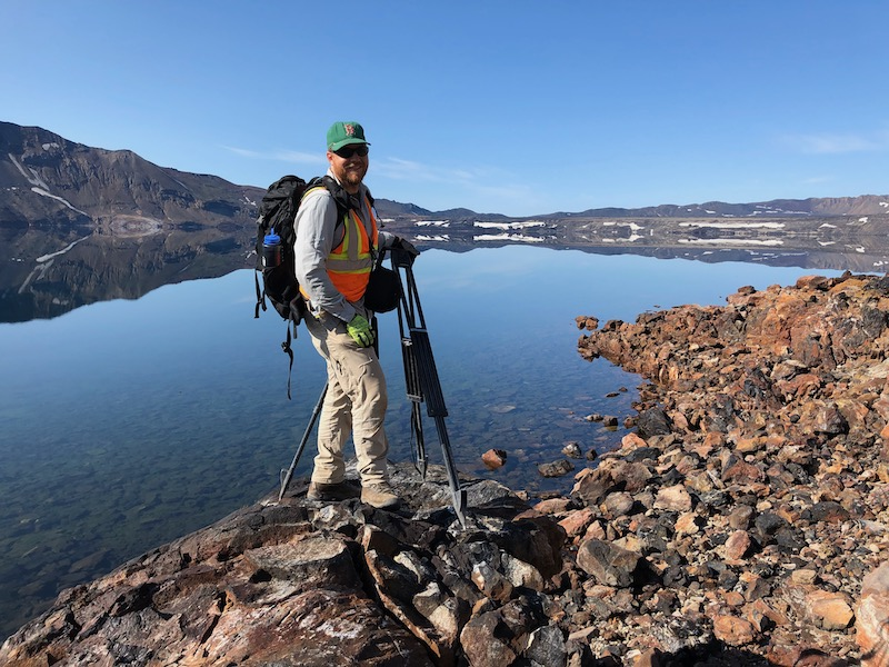 Smiling man at lake with hiking gear and tripod.