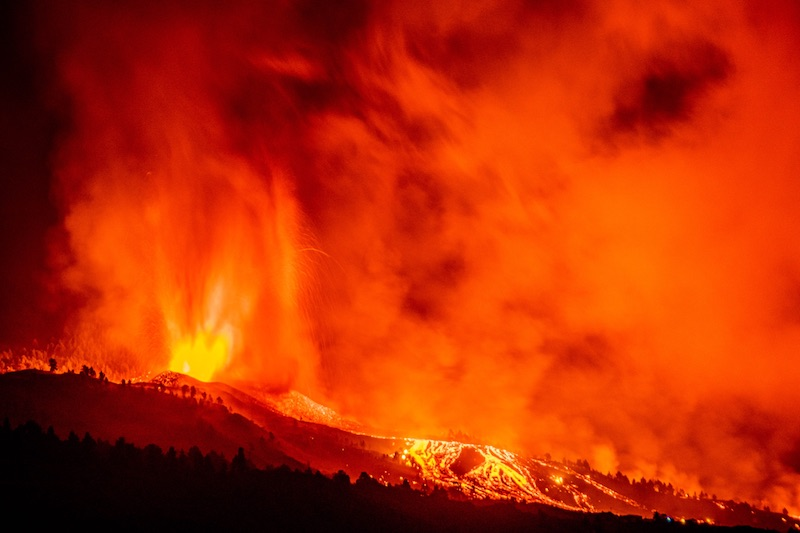 Low black silhouettes and shining yellow streaks of lava beneath a sky almost totally a vibrant red-orange blur.
