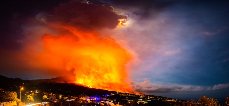 The sky, half blue and half vibrant flaming red-orange clouds, over city lights on a hill.
