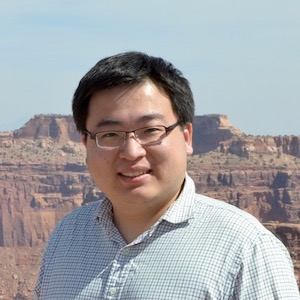 Smiling man with eyeglasses and canyon behind him.