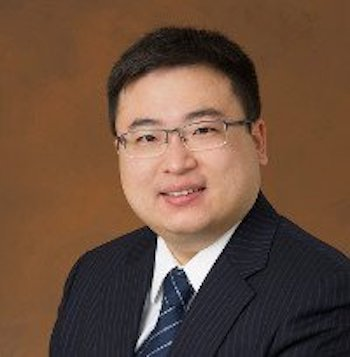 Smiling man with eyeglasses in suit and tie.