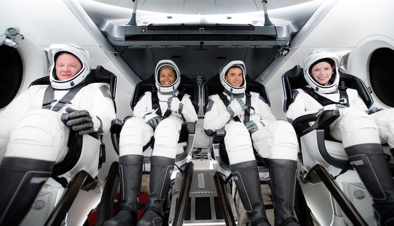Inspiration4: 2 men and 2 women all in white spacesuits strapped into seats inside a small cabin with portholes.