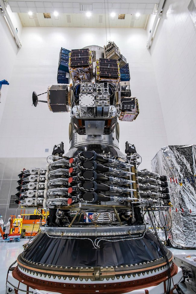 SpaceX lasers: A tower of technical parts and machinery, colored mostly black and silver, sits in a white room.