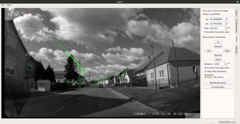 Street with houses with green marks on them, with green line of fireball's path.